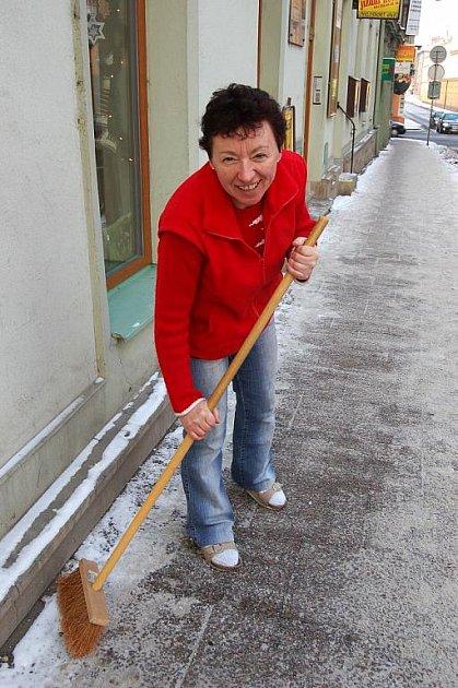 Paní Ratajová z Bolatic odklízí sníh na Pekařské ulici před obchodem, ve kterém pracuje.