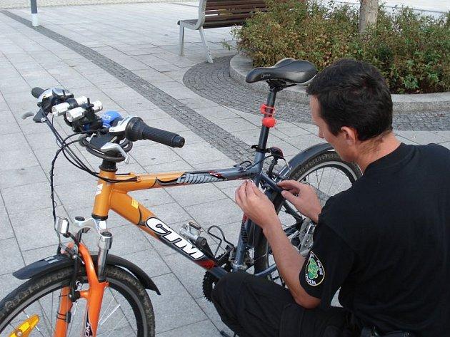 Strážník instaluje na kolo forenzní značení, které v případě odcizení usnadní jeho dohledání.
