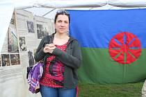 Ředitelka Eurotopie Petra Večerková vedle romské vlajky. Ta je složena ze zelené a modré části coby trávy a nebe. Zároveň se na ní nachází kolo symbolizující přemisťování a cestování.
