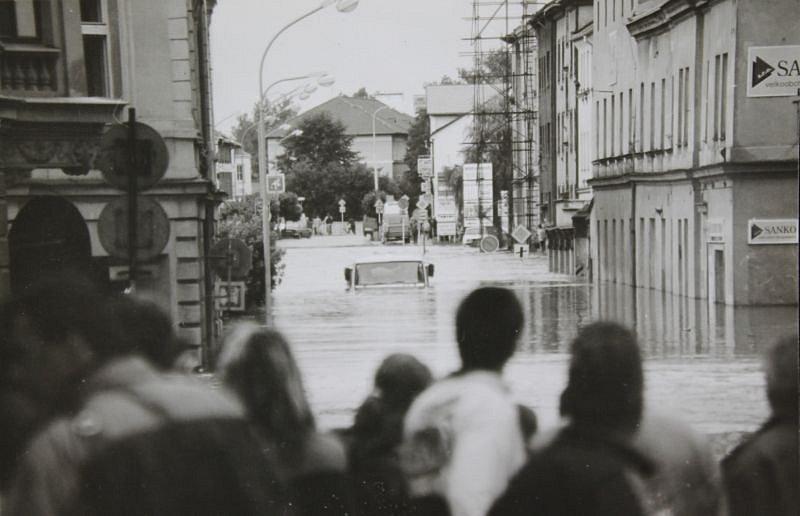 Shromážděný dav před Nákladní ulicí. Vzadu je vidět voda v ulici Pekařské.