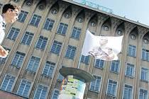 Leopold Bauer vyobrazený na praporu před jeho dílem, nyní opuštěným obchodním domem Breda.