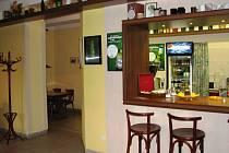 Interiér kavárny Café Parking. Muž se posadil do uličky vlevo od baru. Snad proto, aby na něj nebylo vidět.