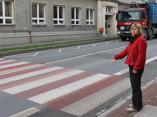 Ludmila Říčná ukazuje na přechod ve Vrchní ulici. Kvůli frekventované dopravě zde přejdete jen stěží.
