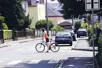 Typická situace. Cyklistka na Fügnerově ulici v Opavě se rozhlíží na nepřehledné křižovatce.