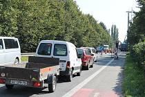 Zatímco kolony aut čekají na semaforech, dělníci pracují na stavbě za pomocí těžké techniky. Zeleň po pravé straně přitom musí ustoupit nové protihlukové stěně.