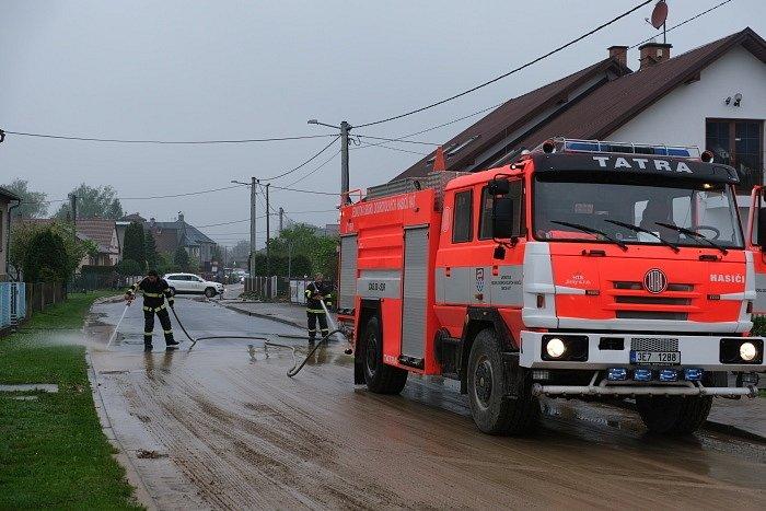 Hasiči pomáhají již dlouhé hodiny v obcích na Opavsku, které zasáhly středeční noční přívalové deště. Hať, 13. května 2021.