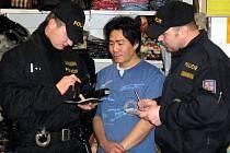 Cizinečtí policisté kontrolují vietnamského prodejce.