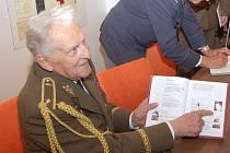 Brigádní generál Alexandr Beer při podpisování knihy, ve které se píše i o něm.