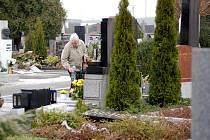 Anna Wernerová upravuje na kateřinském hřbitově rodinný hrob, jemuž se vandalové naštěstí vyhnuli. Sousední hrob jak je na fotografii patrno, však už tolik štěstí neměl.