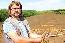 Vedoucí archeologického výzkumu v místech budoucího severního obchvatu Opavy Jiří Juchelka ukazuje pravěký sekeromlat ze zelené břidlice a zhruba deseticentimetrový silicitový nožík, které byly nalezeny v jednom z odhalených hrobů.