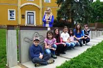 Děti sedí u fragmentu osmnáctého poledníku, který prochází Pustou Polomí. Tato fotografie je součástí dokumentace celého projektu.