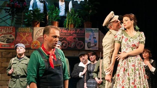 Zleva Nemorino (Juraj Nociar) s nelibostí sleduje flirtování Adiny (Tereza Kavecká) se seržantem Belcorem (Alexander Vovk).