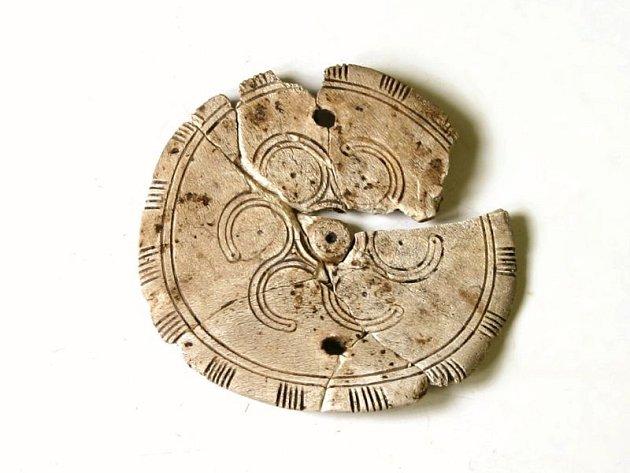 K nalezeným pokladům patří zdobený kostěný terčík a hliněný pohár.