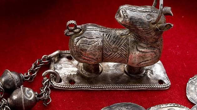 """Drobná zvířecí plastika a mince z pokladu v Komárově, objeveného v roce 1881. Soška je v současnosti v odborné literatuře známá jako """"komárovský beránek"""" (Agnus dei)."""
