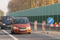 Řidiči projíždějí kolem nové protihlukové zdi na Rolnické ulici. Stále je zde zdržují semafory.
