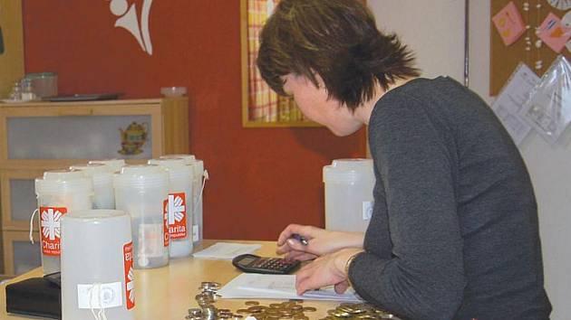 Pracovnice charity počítá obsah sbírkových kasiček.