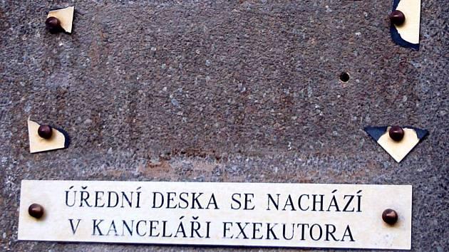 Kde je úřední deska?  Podle této cedule je v kanceláři exekutora na Bochenkově ulici. Podle policejních informací ji však ukradl neznámý vandal, který na exekutory už několik měsíců útočí.