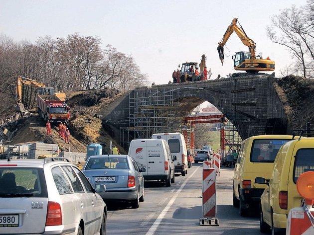 Řidiči stojící na semaforu před viaduktem u Hlučína mohou sledovat scénu, kterou korunuje bagr pracující přímo na vrcholu mostu.