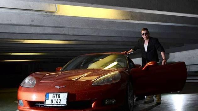 Raper Mike Angelow vedle luxusního automobilu Chevrolet Corvette, který v závěru klipu vybuchne.