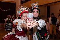Ilustrační snímek, vratné kelímky v akci. Na snímku krojovaný pár s vratným kelímkem s logem chasy na krojovaném plesu v Hustopečích.