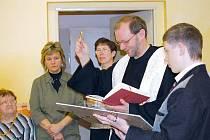 Matěj pomáhá knězi pokřtít své dílo.