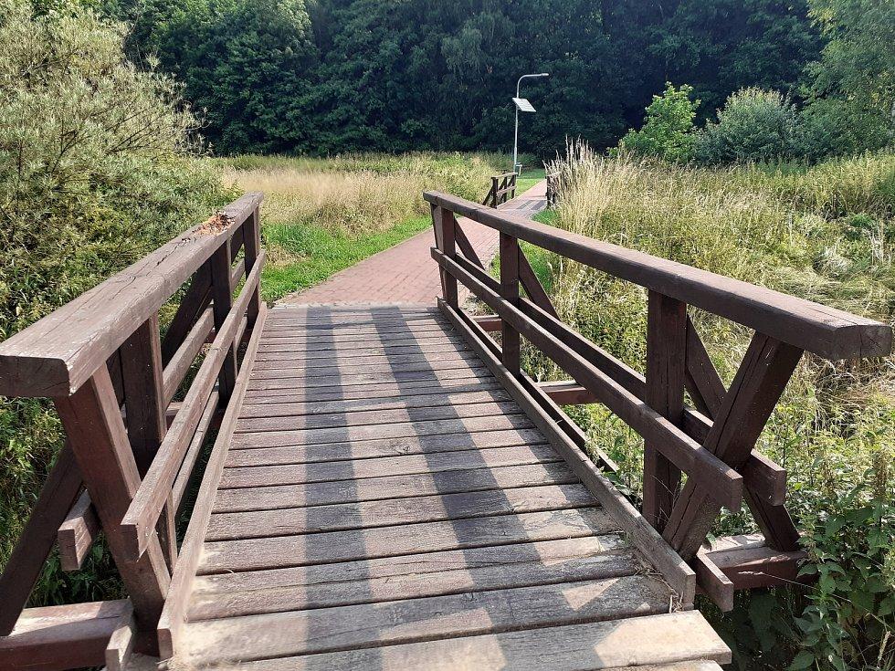 Mostek k prameni, křesťanskému labyrintu a bazénkům.