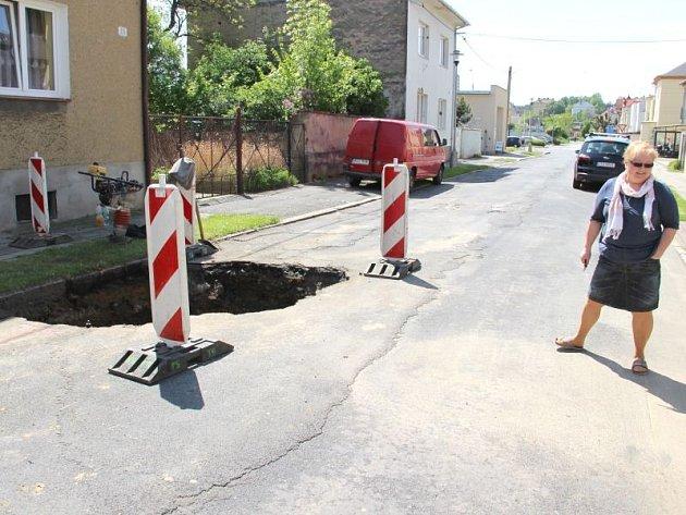 Jana Zwingrová v úterý dopoledne u propadlé silnice v Anenské ulici. Díra vznikla jen pár metrů od jejího domu a pouze se štěstím se nikomu nic nestalo.