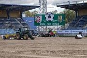 Od čtvrtečního rána se na hrací plochu stadionu pokládá nový pažit.