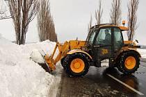 Bagr odklízí sníh na silnici mezi Komárovem a Novými Sedlicemi, kde