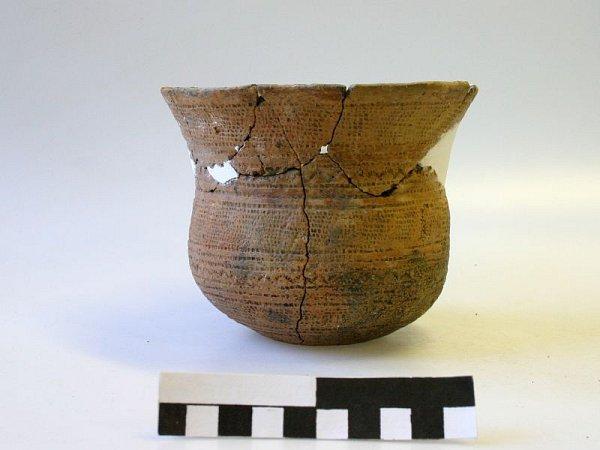 Knalezeným pokladům patří zdobený kostěný terčík a hliněný pohár.