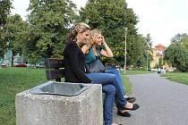 Dívky sedí na lavičce v parku Joy Adamsonové v Opavě. Mimo centrum jsou odpadkové koše často k vidění pouze u autobusových zastávek nebo právě  laviček v parcích.