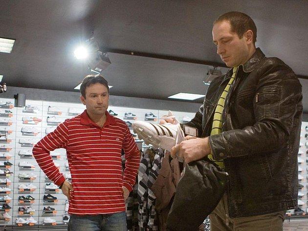 Tomáš Kretek v prodejně D–sportu v Opavě. Manažer obchodu Petr Remeš mu dává kopačky k vyzkoušení.