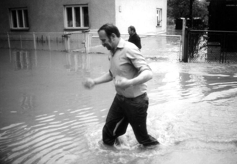 Dva muži ze Smolkova, jejichž domovy jsou již zaplaveny, se brodí špinavou vodou.