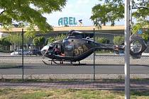 Vrtulník nemohl na staveništi přistát, proto čekal na parkovišti nedaleké firmy.