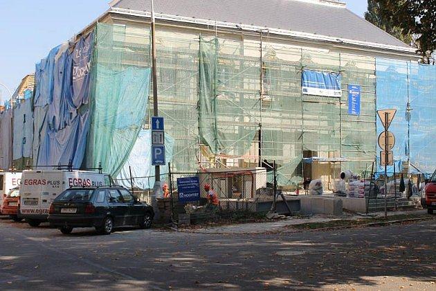 Kulturní Dům Na Rybníčku je schován za průsvitnou sítí. Pracuje se na něm  i o víkendech.