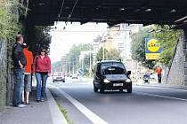 Kvůli úzkým chodníkům pod železničním mostem se zde protijdoucí jen komplikovaně vyhýbají. Chodci na fotografii to zvládli, ale jsou i takoví, kteří raději obcházejí po silnici.
