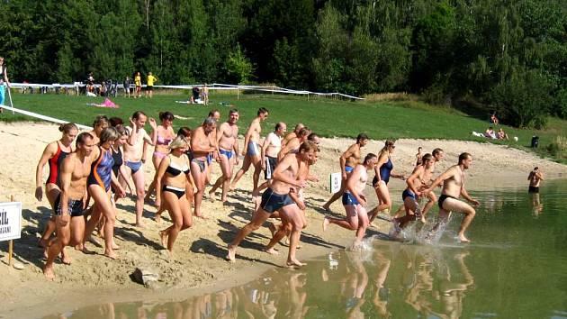 Sedmadvacet aktérů triatlonu na startu plavecké části u Stříbrného jezera.