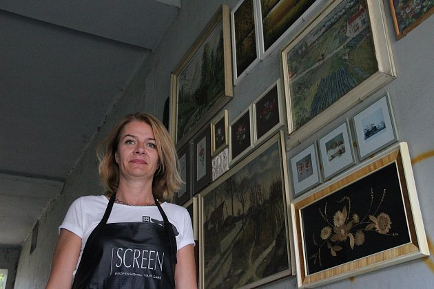Za vyvěšením obrazů v opavském průchodu stojí Olga Malá.