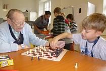 Chlapec hraje společenskou hru s obyvatelem domova pro seniory Vila Vančurova.