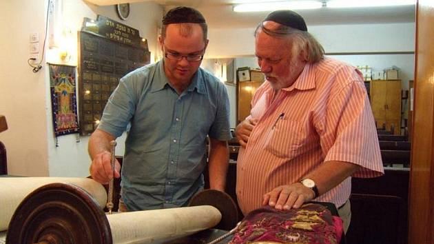 Pavel Kuča (vlevo) čte z krnovské Tóry pomocí ukazovátka zvaného Jad. Praktikující židé totiž čtou z Tóry s takovou úctou, že se nesmí textu dotknout rukou. Krnovským turistům v Izraeli Tóru představil předseda sboru Gideon Mamroth (vpravo).