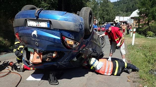 Vyprošťování řidiče renaultu převráceného na střechu v Nových Heřminovech.