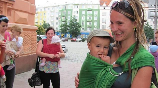 """Deset maminek a jeden tatínek, kteří dávají přednost nošení dětí před kočárkem, se vydali na společnou procházku centrem Krnova. Propagují nošení dětí """"tělo na tělo""""."""