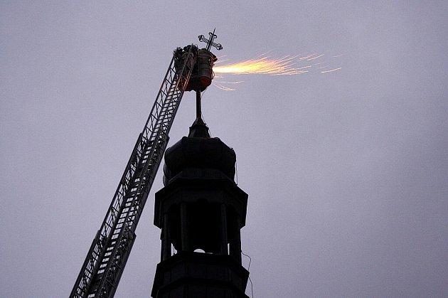 Teprve s pomocí nejdelšího automobilového žebříku v Moravskoslezském kraji, který dovezli do Krnova z Ostravy, se podařilo místním hasičům odřezat a sundat dva metry vysoký nakloněný železný kříž na věži minoritského kostela v centru města.