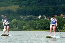 Na surfu s pádlem. Na Petrově rybníce v Krnově zkouší lidé nový druh sportu.