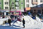 Krnovské děti radostně dovádí na hromadě sněhu přímo na náměstí.