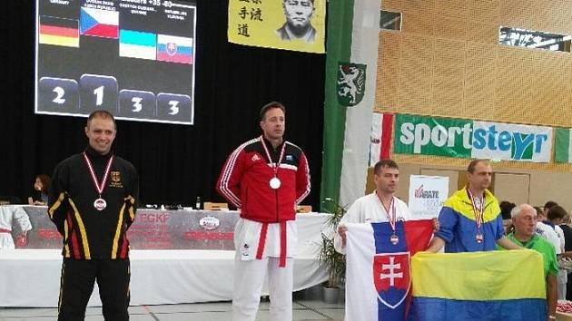 Bruntálský karatista David Dvořák (uprostřed) obhájil v Rakousku na evropském šampionátu titul, když ve finále porazil borce z Německa.