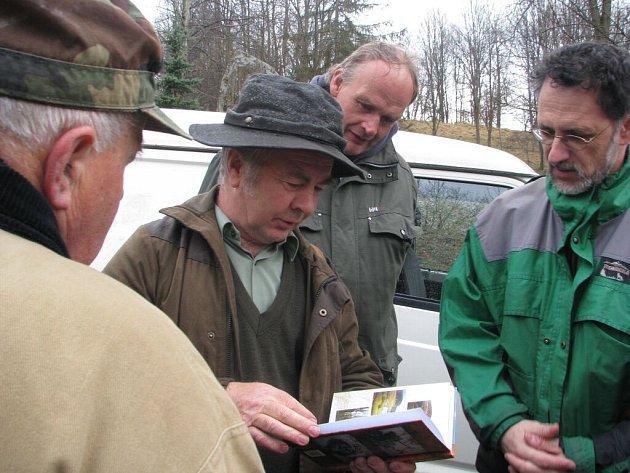 Účastníci zájezdu z Krnova a Bruntálu si prohlíží knížku Jindřicha Machaly Kronika Libavska. V sobotu si mohou prohlédnout krásy Libavé na vlastní oči.