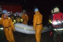 Hasiči s člunem se vydávají přesvědčovat občany Linhartov, aby se nechali evakuovat.