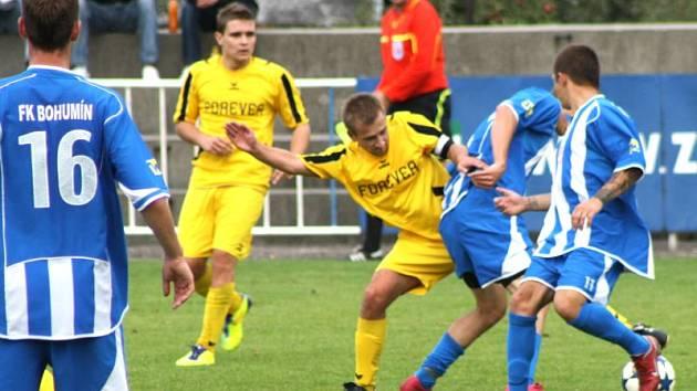 Krnovští fotbalisté budou na hřišti Frýdku-Místku spoléhat také na výkon svého kapitána Ondřeje Bartoníčka (na snímku uprostřed bojuje s hráči Bohumína).