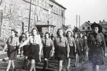 Průvod junáků po znárodnění průmyslu v roce 1946 městem Bruntál. Na zdech bývalé nemocnice jsou ještě ochranné krycí malby před bombardováním.